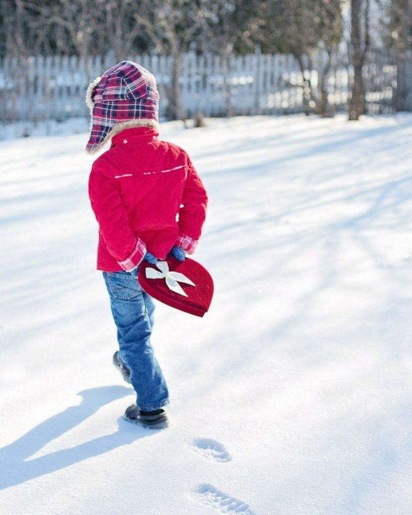 Image of boy walking on snow with valentines gift in hand.
