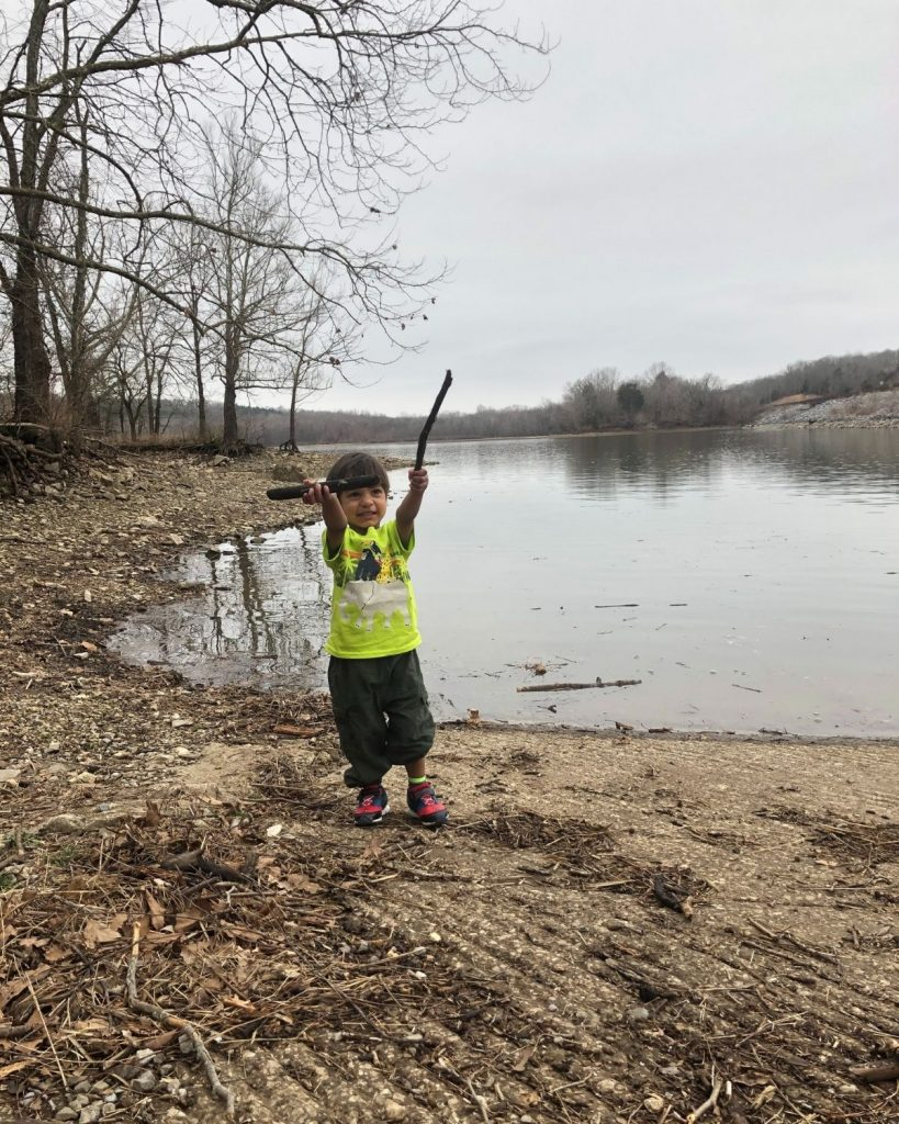 Image of toddler boy holding up sticks by a lake.