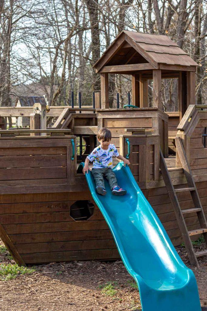 Image of toddler playing in slide at Huntsville Botanical Gardens.