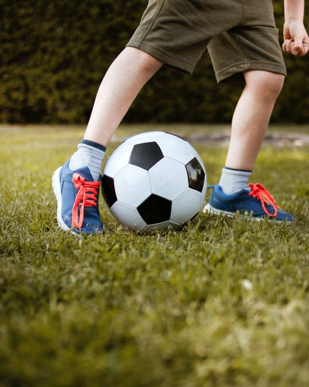 Closeup image of a kids feet kicking a football.